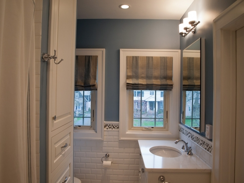 Custom roman shades and blue painted walls add depth to the mostly white master bathroom.