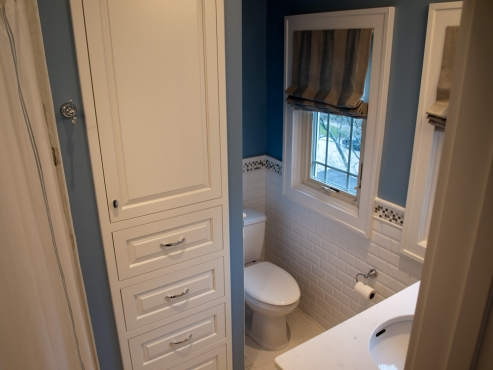 Secluded toilet area with a floor to ceiling linen closet for bathroom storage.