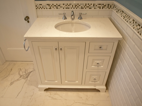 Tailor-made vanity with Rohl faucet, quartz countertop and polished chrome cabinet hardware.