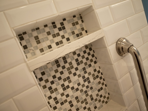 A recessed niche backed with stone and glass mosaic accent tile provides storage space in the shower.