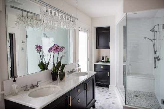 "The oversized, walk-in shower boasts a custom bench, floor to ceiling glass panels and updated classic features, such as the white 2x8 subway tile and 1"" hexagon floor. A linen cabinet and coffee bar combo is tucked in the corner of the bathroom, allowing for convenience, as well as extra storage space."