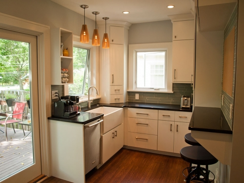 Traditional elements with contemporary flair is the hallmark of this kitchen. Custom-made floor to ceiling cabinetry with full-overlay slab style doors with satin nickel knobs and pulls utilize every inch of the space.