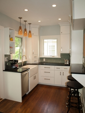 Dark quartz countertops off-set the bright, white cabinetry and dark, hardwood floors bring warmth to an otherwise, cool-toned kitchen. New Pella windows allow for tons of natural light.