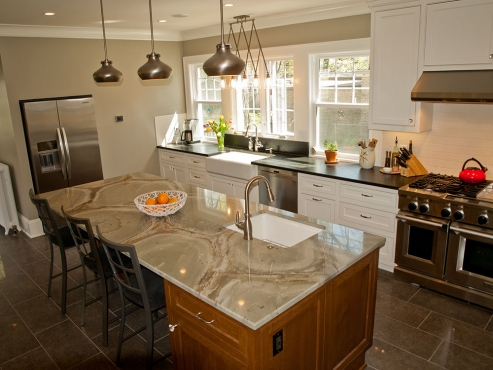 The unique quartzite countertops and Feiss light fixtures add distinctive character to the kitchen. The black leathered granite and white cabinetry along the perimeter of the room is offset by the one-of-a-kind quartzite and quarter-sawn oak island. The island base was specifically built to match the original quarter-sawn oak hardwood floors throughout the home.