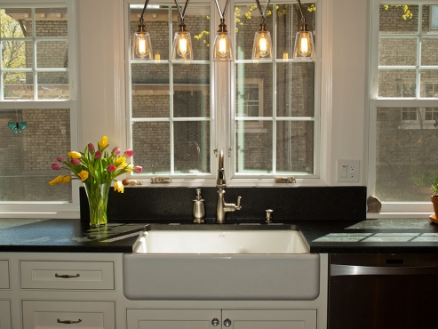 The black leathered granite countertops are brightened by the cast iron farm sink and ample natural light flooding in from the new windows.