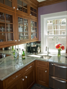 The original butler's pantry was updated with new custom cabinetry, hammered bar sink, and beverage refrigerator.