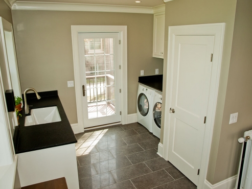 A side-by-side washer and dryer left room for counter space and supplementary storage. The same porcelain floor tile and black granite from the kitchen were used to keep the two spaces cohesive.
