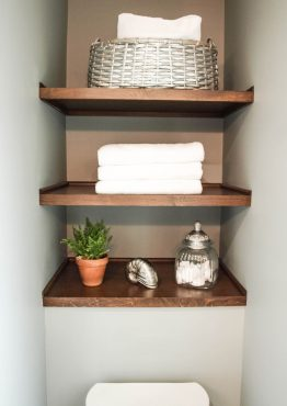 Custom open shelving, stained to match a client's accessory piece, brings warmth to the otherwise cool-toned space.