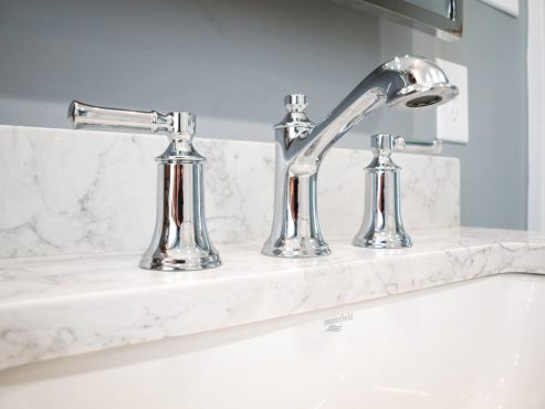 Chrome widespread faucets with traditional lines complete the double vanity.
