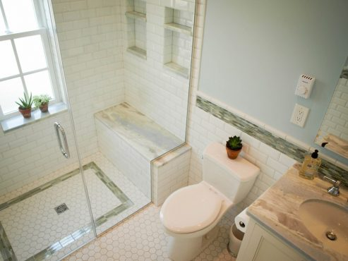 Beautiful glass accents on the shower floor and walls of bathroom bring out the veins on the marble shower bench seat.
