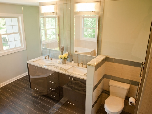 The chocolate-stained, custom-built vanity coordinates perfectly with the porcelain tile floors.