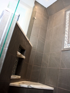 A custom-cut glass shower enclosure makes the shower appear larger while the stone and glass mosaic tile and Calacatta marble accents brighten the space.