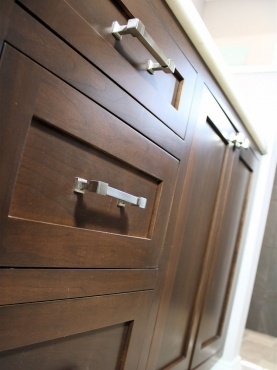 Dark stained wood cabinetry with brushed nickel cabinet hardware brings natural warmth to the master bath.