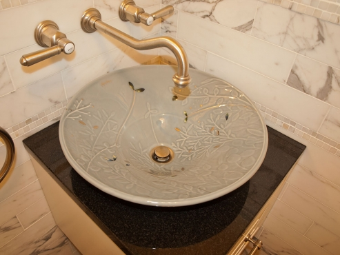 The Kohler above-counter sink and wall-mounted faucet make a sophisticated design statement in the small space.