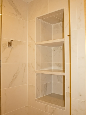 Oversized, custom niches in shower entry allow for plenty of additional storage.