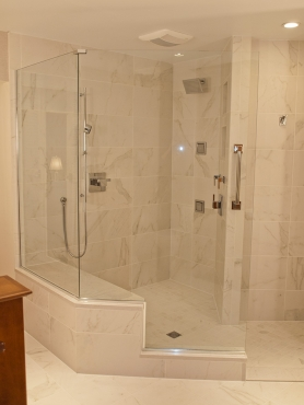 This walk out curbless shower has custom 3/8 inch thick tempered glass that compliments the clean lines of the Caesarstone bench.