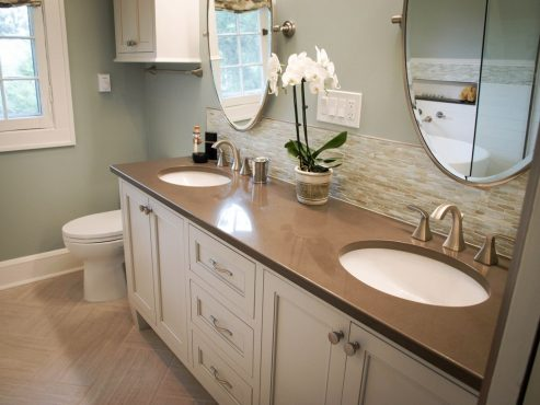 A one-of-a-kind vanity designed for the space with glass tile backsplash and pivoting wall mirrors.