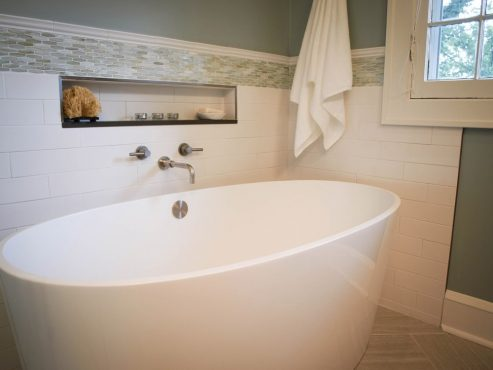 Beautiful soaking tub with towel, soaps and razor within effortless reach.