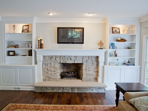 The original brick surround was refaced with ledger stone and the brick hearth was replaced with a limestone slab. Custom built-in bookcases with lower storage cabinets coordinate with the new mantel. Wood floors refinished with a darker stain, crown molding and a fresh coat of paint complete the family update.