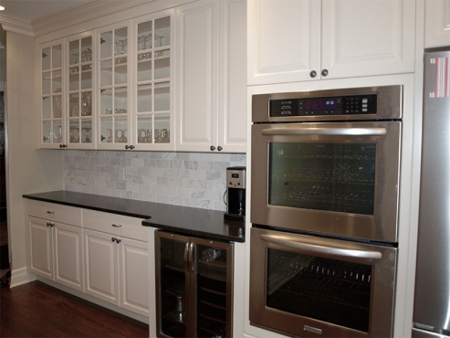 Double ovens, a wine cooler and custom glass front cabinets add form and function to this dream kitchen.