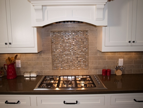 Six burner range set into beautiful chocolate quartz counter tops. A commercial grade exhaust hood is barely visible. Unique hand-made glass tile mosaic backsplash compliments the cooking area.
