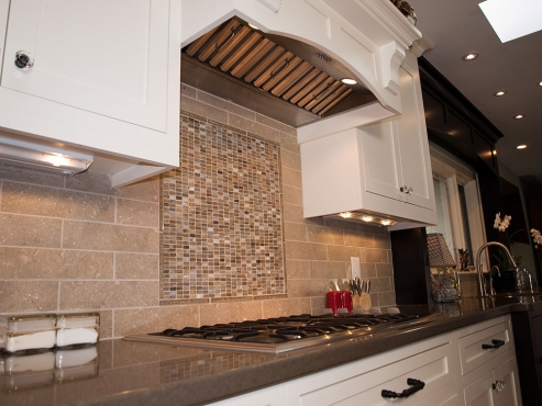 A different view of the concealed exhaust hood and glass mosaic surrounded by long ceramic subway tile.