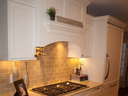 Six burner range, pot filler and concealed commercial grade hood with ten-inch vent. The Beard Group removed the servant's staircase to make room for this area.