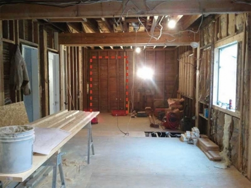Floor leveled, new sub-floor down, second floor bathroom plumbing re-routed and new support beams in place. Time to build a kitchen! Notice future opening from kitchen to living room.