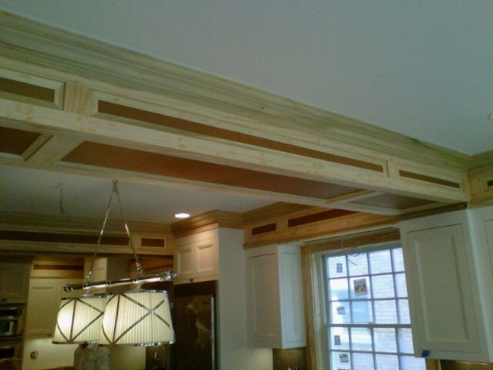 Custom woodwork on soffits to copy the door profile of the cabinets.