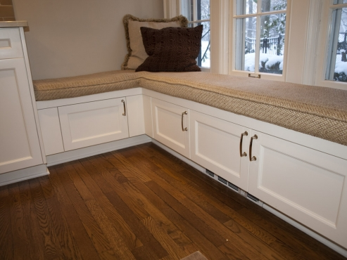 Additional storage located below cushioned bench seat in cocktail corner.