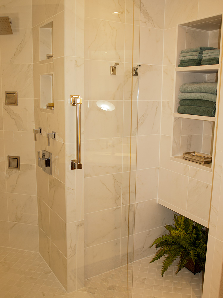 In the drying area of the shower, recessed floating shelves made of Caesarstone store clean, dry towels.