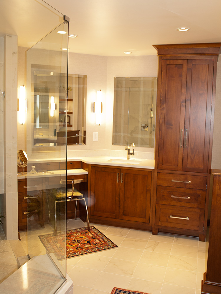 Custom cabinetry lines the bathroom featuring a makeup vanity, separate sink, and linen closet.