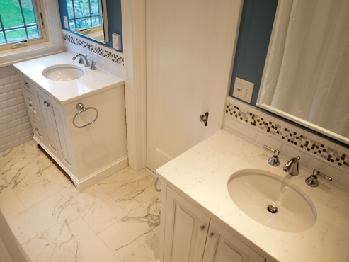 His and her vanities with Rohl faucets and quartz countertops flank the bathroom door.