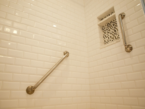 Polished chrome grab bars and a recessed niche add functionality to the shower.