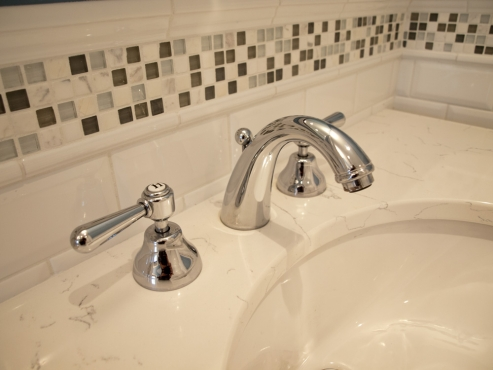 Rohl faucet with stone and glass mosaic accent tile are classic touches to this master bathroom.