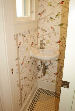 Cheerful songbird wallpaper and multicolored cement floor tiles adorn the small powder room. A corner wall mounted sink makes the best use of the limited space.