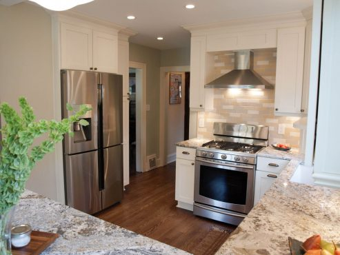 Upper cabinets over the fridge and a pull-out pantry add much needed storage space to the kitchen.