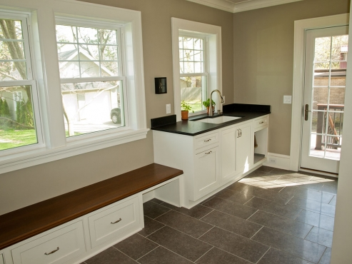 The light filled laundry and mudroom room includes bench seating, additional storage space and a utility sink.