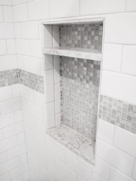 A shower niche tiled with the mosaic accent tile adds storage to the shower.