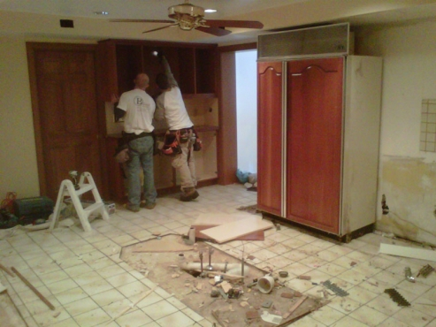 Tearing down the old outdated kitchen cabinets to make way for new ones.
