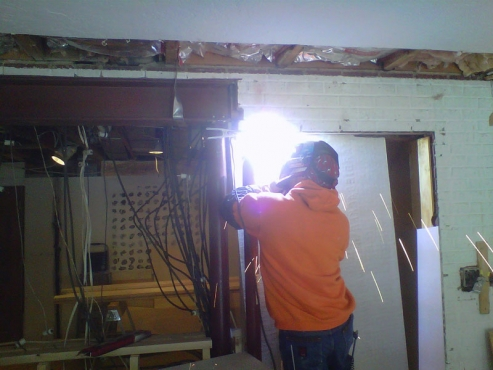 Expert welder Rickey Tanno securing 10 inch steel I-beam to support posts above new breakfast bar opening