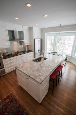 The kitchen features a large island with sink.  The dark perimeter countertops contrast with the light island stone.  Plenty of storage for a growing family.