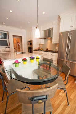 The end of the island features a floating table with custom steel fabrication and rounded tempered glass.  A nice natural light filled space to enjoy a home cooked meal