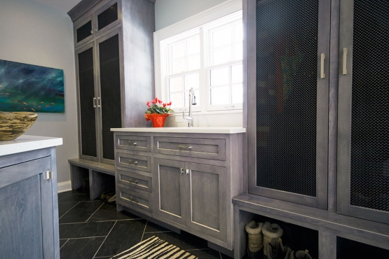 The mud room, formerly the kitchen, has custom cabinets and an extra sink.  With kids in sports, the extra sink comes in handy for those muddy football games. Flooring is slate on a herringbone pattern with a contrasting grout color.