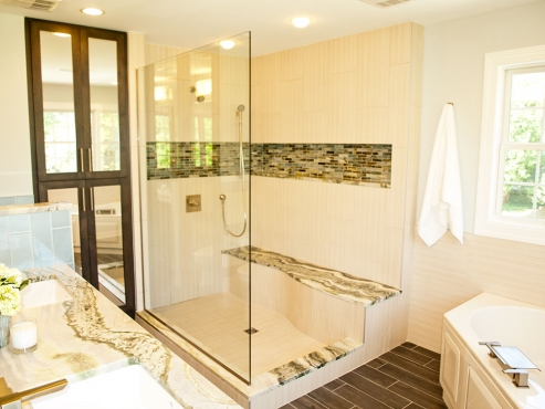 The exposed shower features a custom curved bench, oversized niche and dual shower heads. The Illumi marble bench seat makes a statement against the subtle 12x24 field tile and 1x4 glass mosaic in the niche.