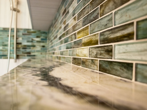 The extensive shower niche has beautiful shades of blue and green that play off the Illumi stone used throughout the space.