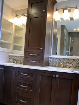 The vanity features dark stained custom cabinets, his and hers sinks with a Calacatta marble countertop, and built-in shelving for additional storage.