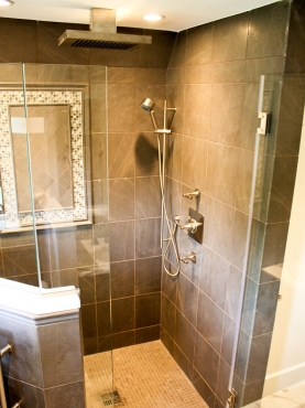 The shower incorporates many luxurious features such as a rain shower head, Gris Foussana limestone tile and brushed nickel shower fixtures.