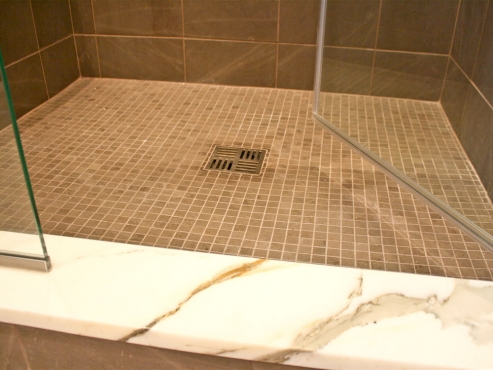 The 1x1 Gris Foussana limestone mosaic tile on the shower floor coordinates with the honed 12x12 Gris Foussana Limestone tile on the walls.