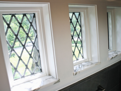 The original lead-glass windows fill the modestly sized bathroom with natural light, making the master bath feel bright and spacious.